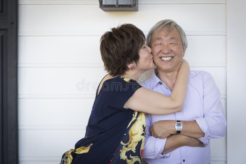Attraktiva kinesiska par som tycker om deras hus arkivfoto