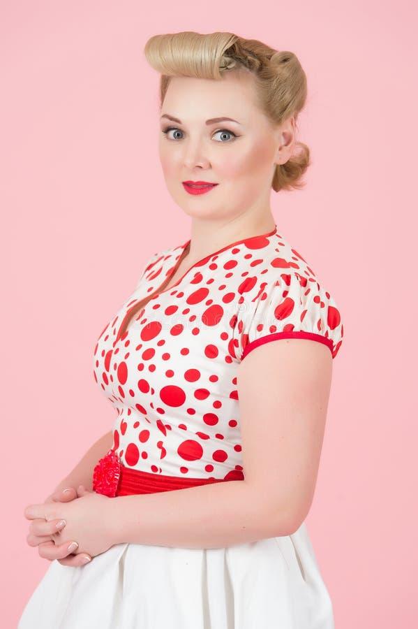 Attraktiva kvinnliga känsliga förtroendeinnehavhänder och utvärdering se kameran Blond kvinna i den vita röda fläckklänningen royaltyfri foto