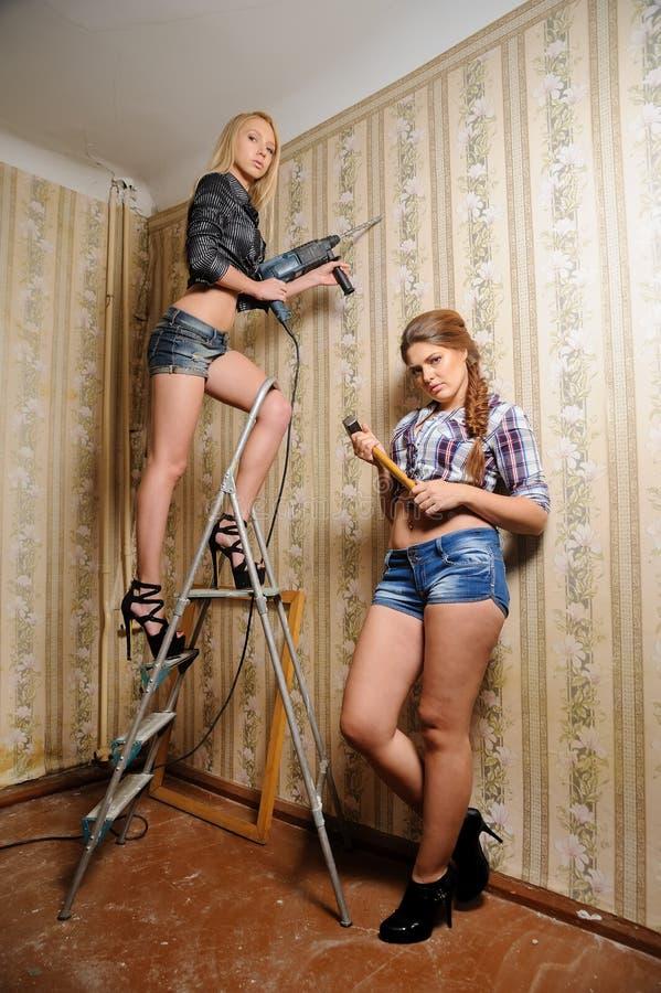Attraktiva kvinnor gör reparation i lägenhet royaltyfria foton