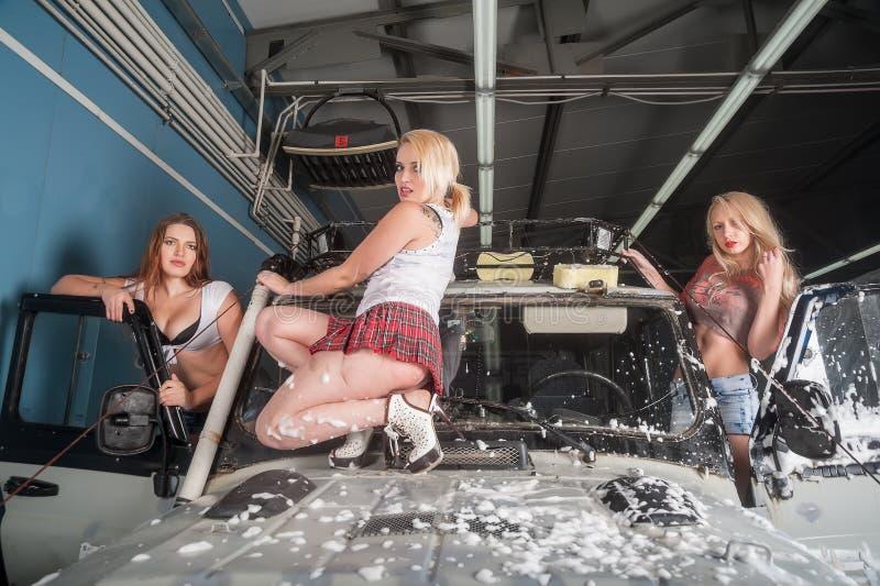 Attraktiva kvinnor som tvättar den offroad bilen royaltyfri bild