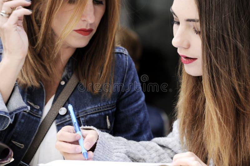 Attraktiva kvinnor undertecknar en överenskommelse i ett utomhus- kafé arkivfoton