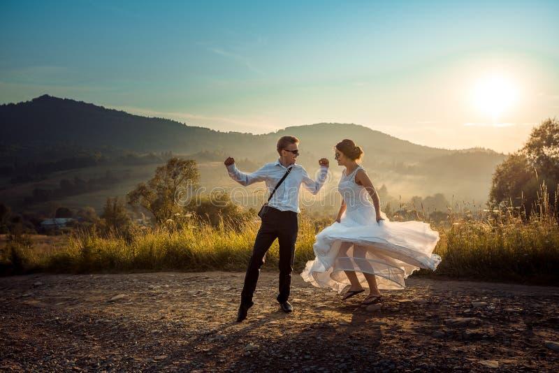 Attraktiva lyckliga nygifta personer har gyckel, medan dansa på vägen i bygden under solnedgången arkivbild