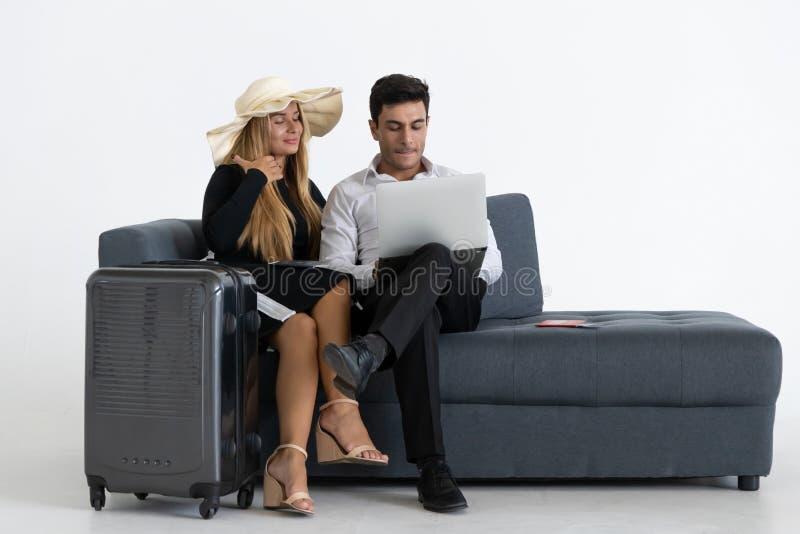 Attraktiva lyckliga par som sitter, och planl?ggningssemestertur Resa resv?skan med seascapeinsida fotografering för bildbyråer