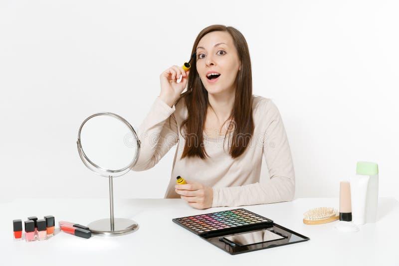 Attraktiva målningögonfrans för ung kvinna med mascara som sitter på tabellen som applicerar makeup med den dekorativa fastställd arkivbild