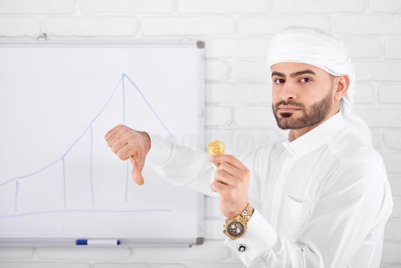 Attraktiva muslim som är allvarliga hållande guld- bitcoin- och visningtummar ner arkivbild