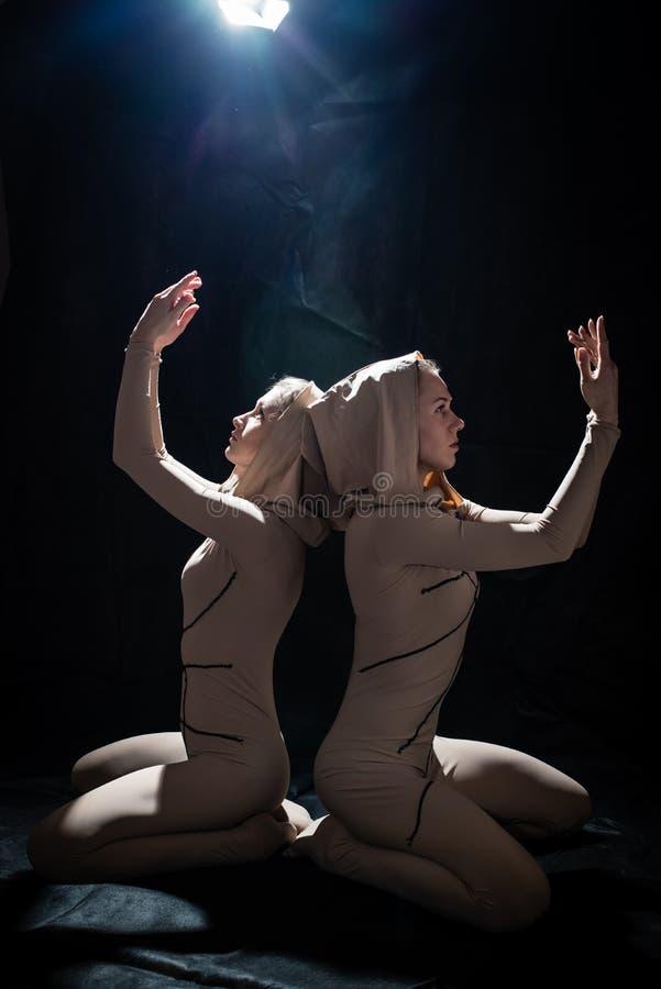 2 attraktiva nätta unga förföriska kvinnor i den åtsittande kropp färgade dräkten som upp ser händer i bön på svart royaltyfria bilder