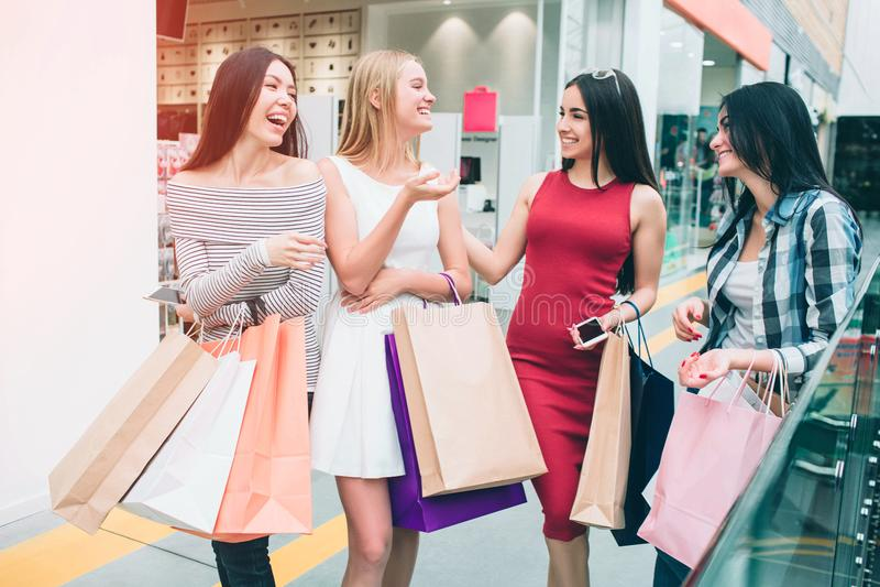 Attraktiva och gladlynta unga kvinnor talar med de och att le De har många shoppingpåsen i händer flicka royaltyfria foton