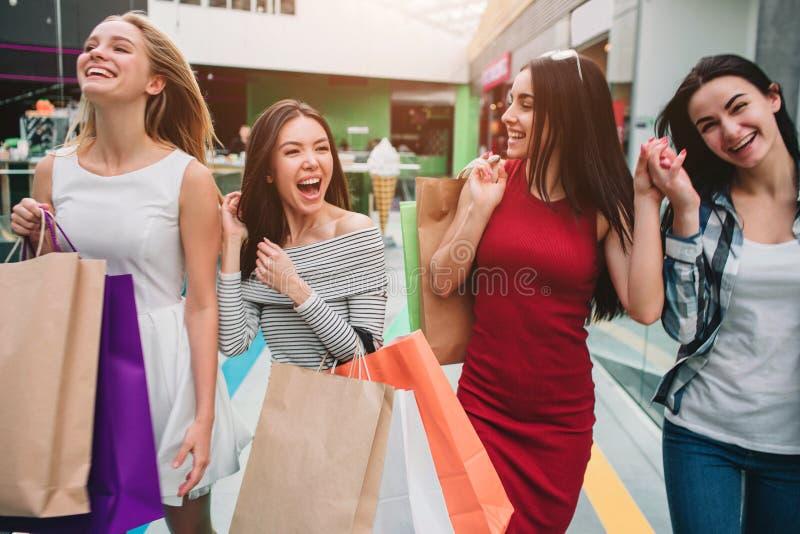 Attraktiva och tillfredsställda flickor går i galleria tillsammans De rymmer påsar med material Flickor skrattar och royaltyfria bilder
