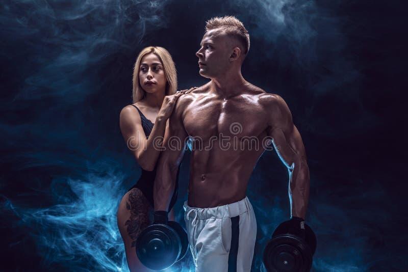 Attraktiva par, en slank blond kvinnlig och den stiliga shirtless grabben som poserar på studion på ett mörker, texturerade bakgr arkivfoton