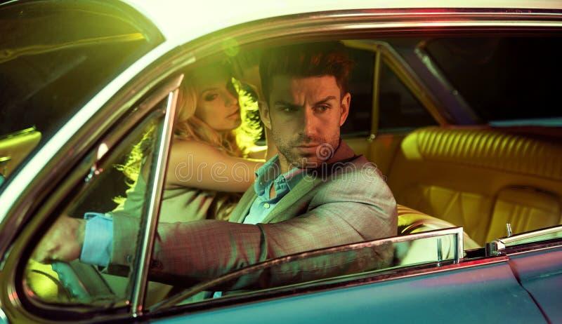 Attraktiva par i den retro bilen royaltyfria bilder