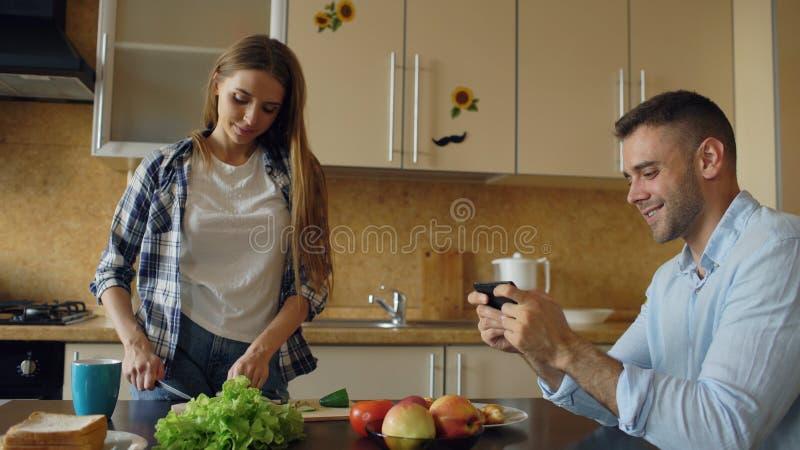 Attraktiva par i köket Man att spela videospelet på smartphonen medan hans flickvänmatlagning arkivbild