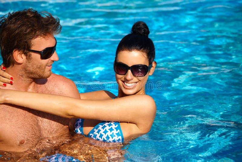 Attraktiva par i simbassäng på sommar arkivfoto