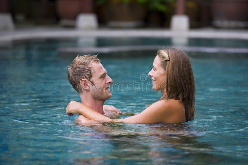attraktiva par pool simning arkivbilder