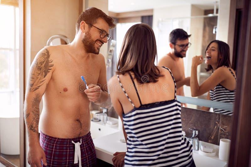 Attraktiva par som borstar tänder i morgon arkivbild