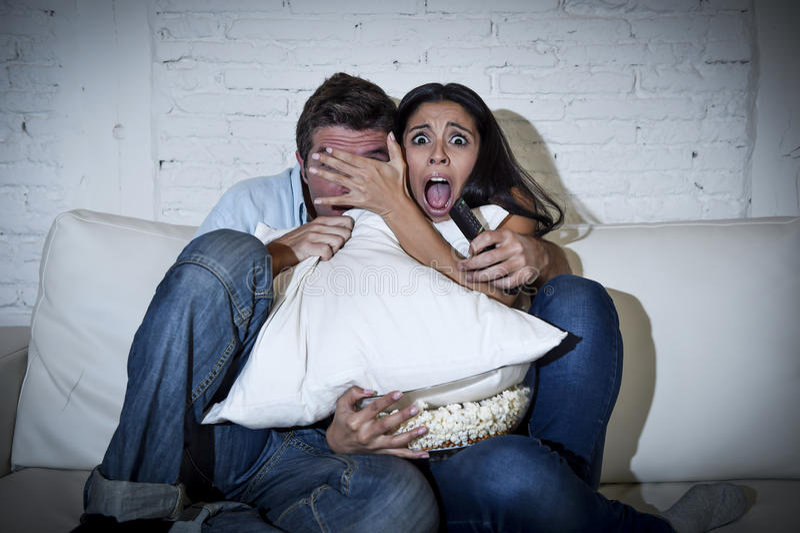 Attraktiva par som har rolig hemmastadd tyckande om hållande ögonen på show för televisionfasafilm royaltyfria bilder