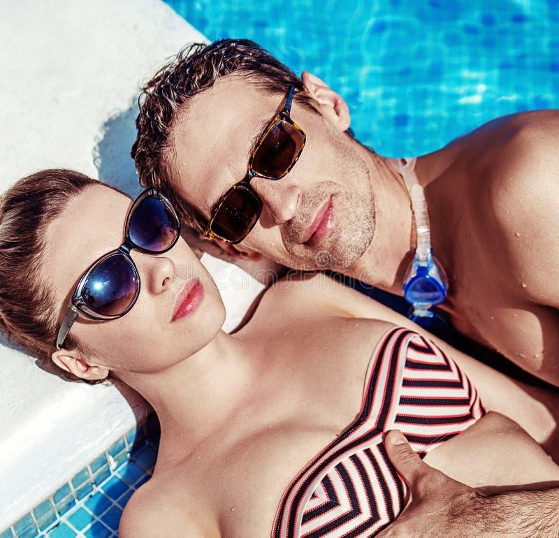 Attraktiva par som kopplar av vid simbassängen royaltyfria foton