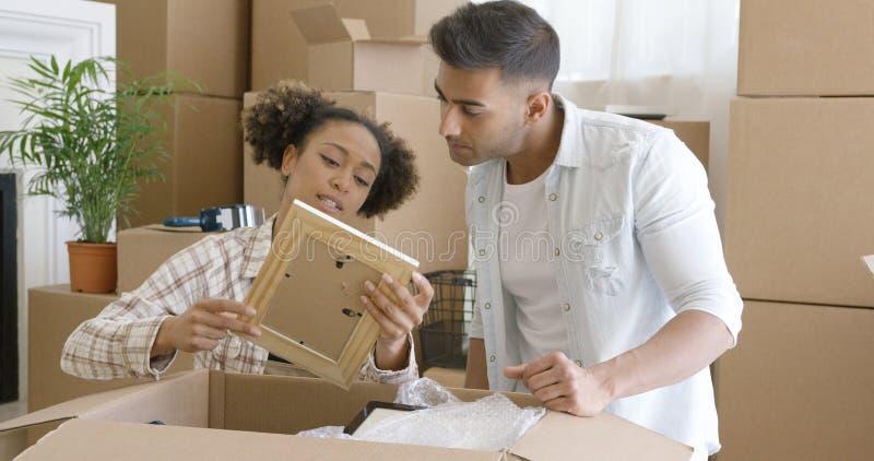 Attraktiva par som packar upp deras saker i nytt hem royaltyfria foton