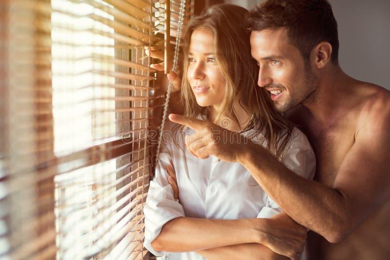 Attraktiva par som ser till och med fönstret royaltyfria foton