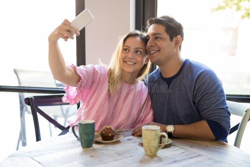 Attraktiva par som tar selfie på restaurangen arkivfoton