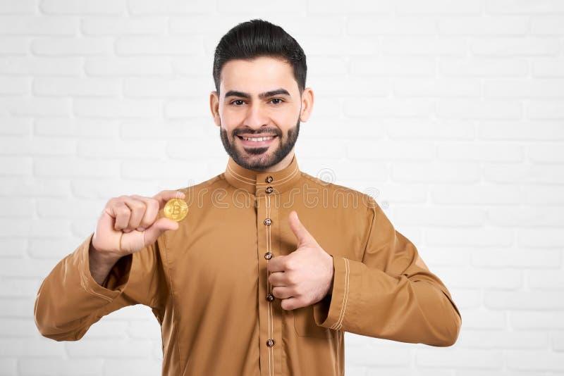 Attraktiva positiva muslim modellerar i traditionella islamiska kläder som rymmer guld- bitcoin och visar upp tummar royaltyfri fotografi