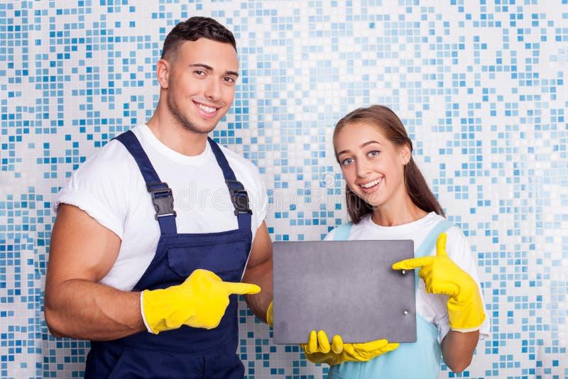 Attraktiva rengöringsmedel gör ren ett hus med gyckel arkivfoton