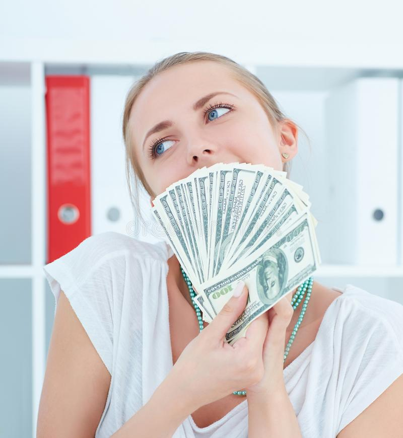 Attraktiva tänkande hållande dollar för lycklig kvinna i händer och önskar att spendera pengar royaltyfri foto