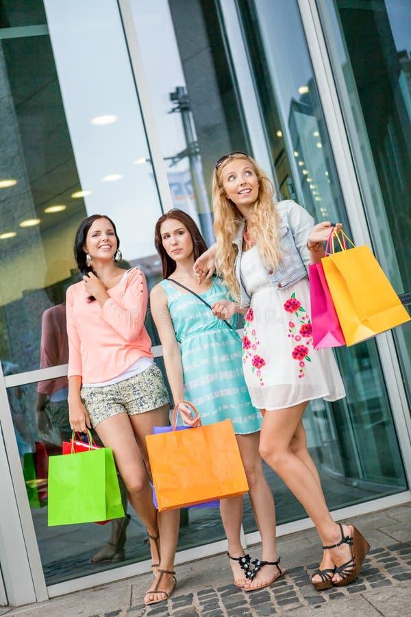 Attraktiva ung flickakvinnor på shopping turnerar arkivbild