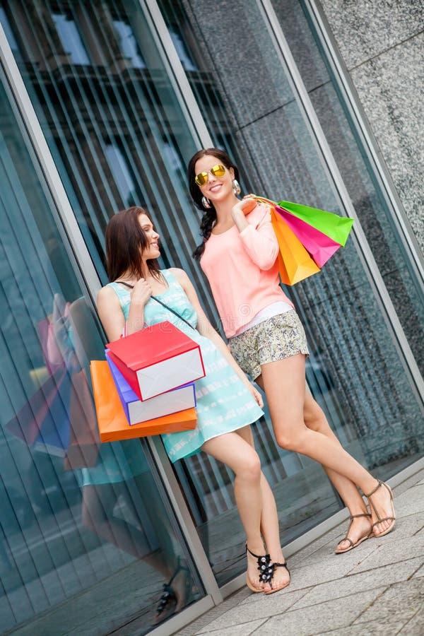 Attraktiva ung flickakvinnor på shopping turnerar royaltyfri foto