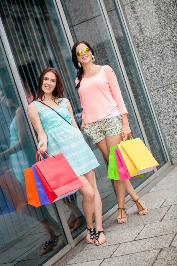 Attraktiva ung flickakvinnor på shopping turnerar royaltyfri bild
