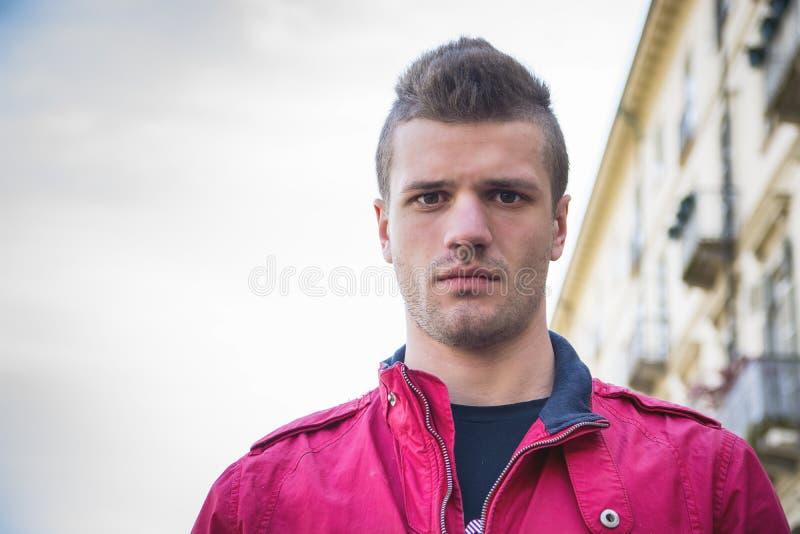 Attraktiva ung mans headshot i stads- inställning arkivbild