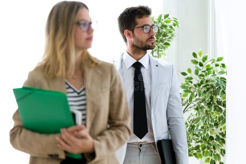 Attraktiva unga affärspartners som från sidan ser i ett hall av dem företag royaltyfri fotografi