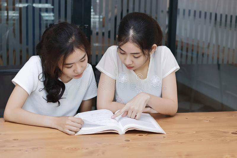 Attraktiva unga asiatiska kvinnor med en bok i vardagsrum royaltyfria bilder