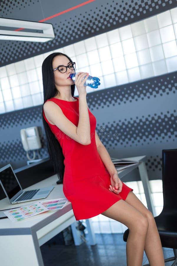 Attraktiva unga businesslady i röd klänning sitter på tabellen i kontors- och hållvattenflaskan fotografering för bildbyråer