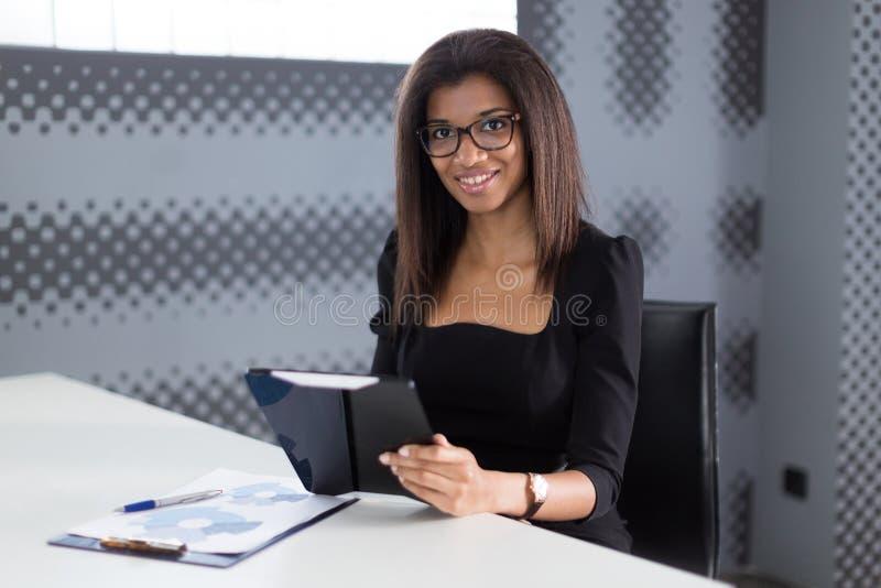 Attraktiva unga businesslady i svart starkt följe sitter på kontorstabellen arkivbilder