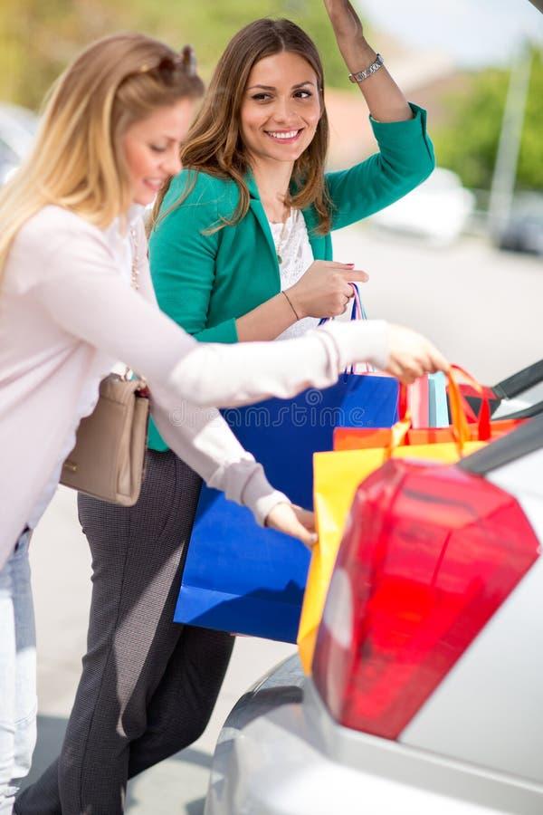 Attraktiva unga flickor sätts påsarna in i bilen arkivfoton