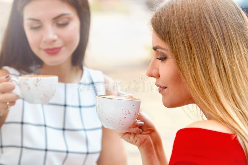 Attraktiva unga kvinnor dricker kaffe i sommarstad royaltyfri foto