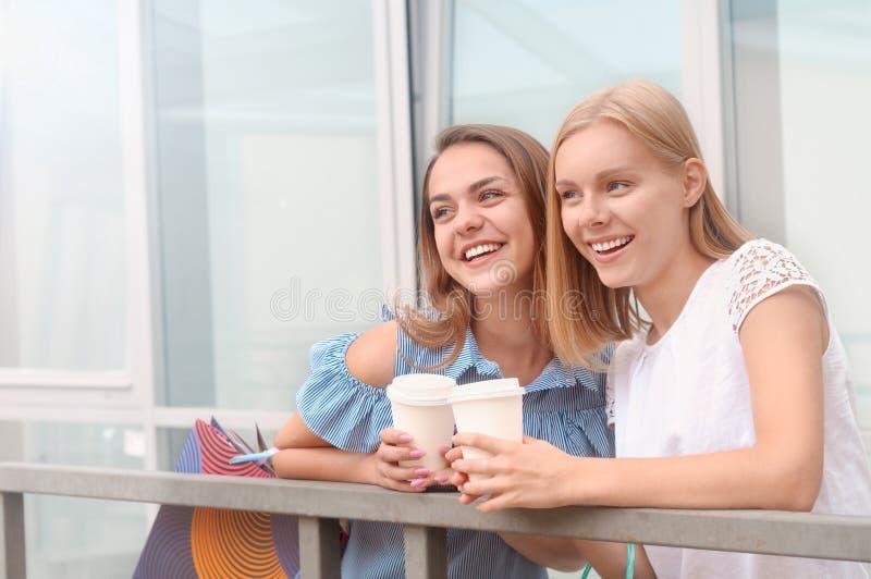 Attraktiva unga kvinnor med bort kaffe för tagande i sommarstad royaltyfri fotografi