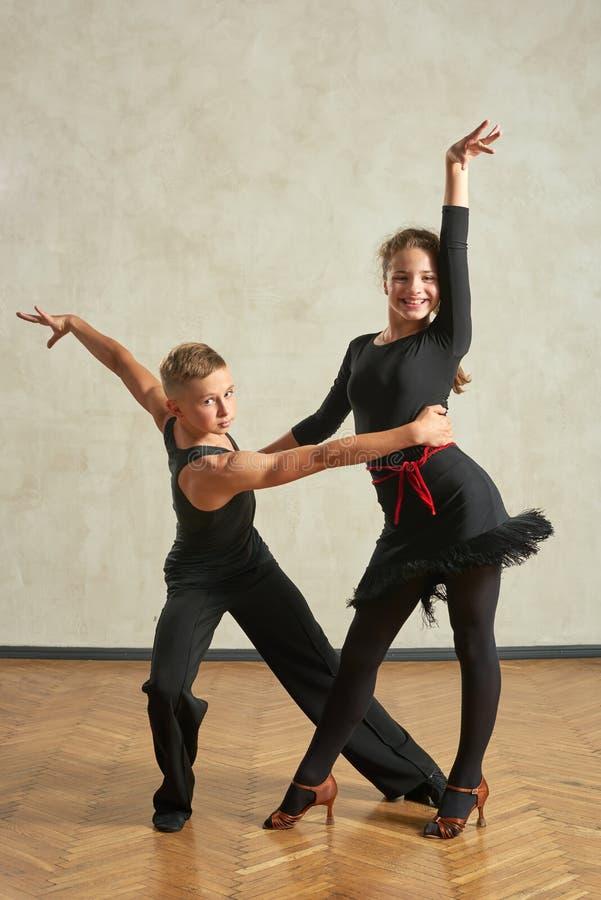 Attraktiva unga par av barn som dansar balsaldans fotografering för bildbyråer