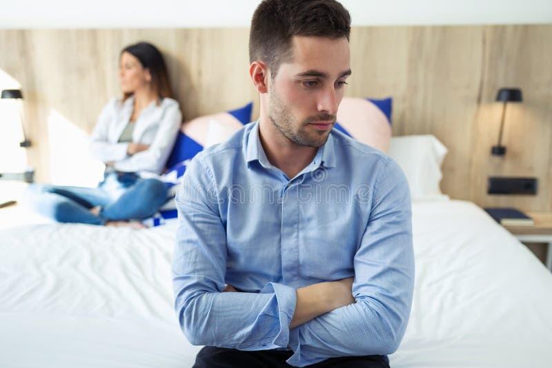 Attraktiva unga par som ignorerar sig efter ett argument som sitter på säng på hotellrum royaltyfri foto