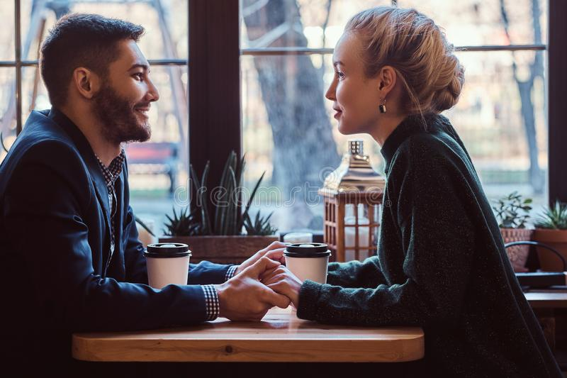 Attraktiva unga par som rymmer händer, ser de och talar, medan sitta i restaurangen royaltyfria foton