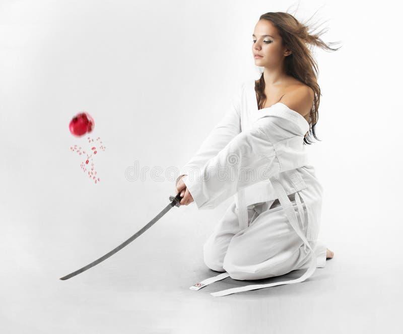 Attraktiva unga sexiga kvinnor med samurajsvärdet arkivfoto