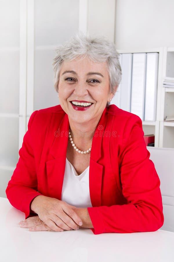 Attraktive ältere ältere Geschäftsfrau, die am Schreibtisch trägt bezüglich sitzt stockfotografie