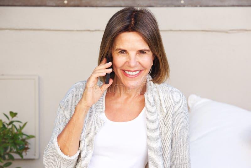 Attraktive ältere Frau, die am Handy lächelt und spricht lizenzfreies stockbild