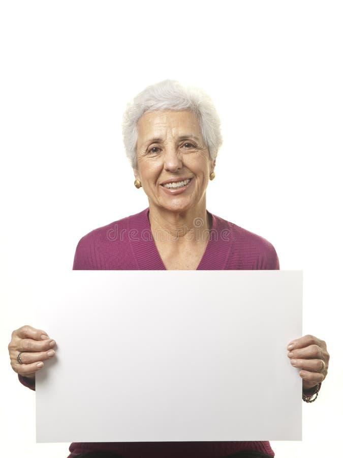 Attraktive ältere Frau, die unbelegte Anschlagtafel anhält lizenzfreie stockfotos