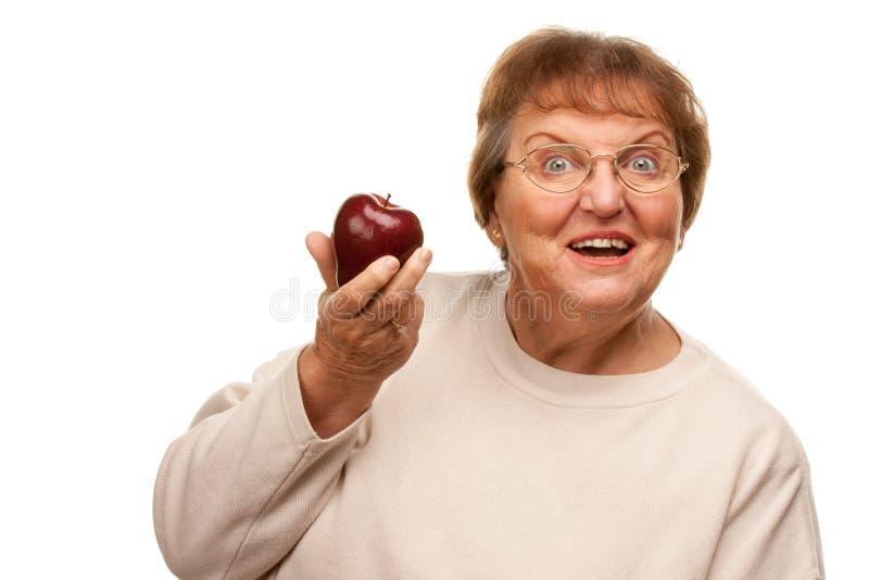 Attraktive ältere Frau mit rotem Apple stockbilder