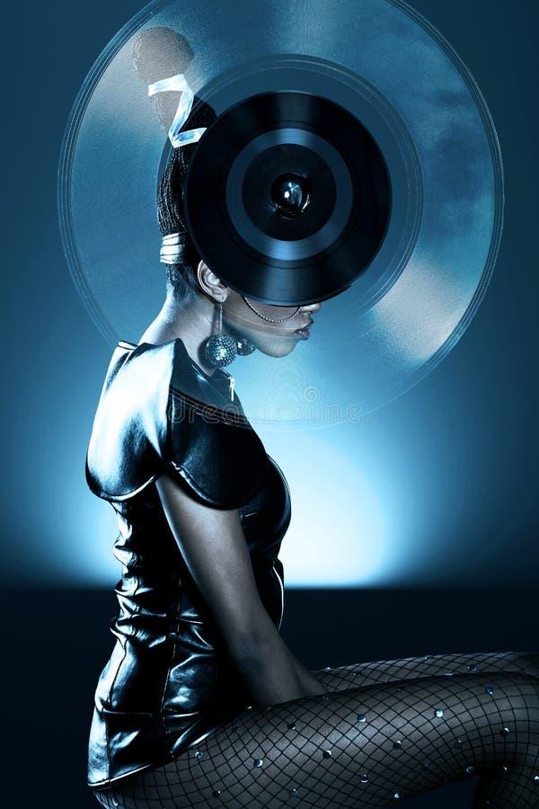 Attraktive afrikanische Frau mit Vinylaufzeichnung auf Kopf lizenzfreies stockbild