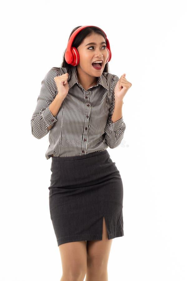 Attraktive asiatische junge Frau, welche die roten Kopfhörer stehen mit dem überraschenden Gesichtsausdruck oben schaut zu ihrer  lizenzfreie stockbilder