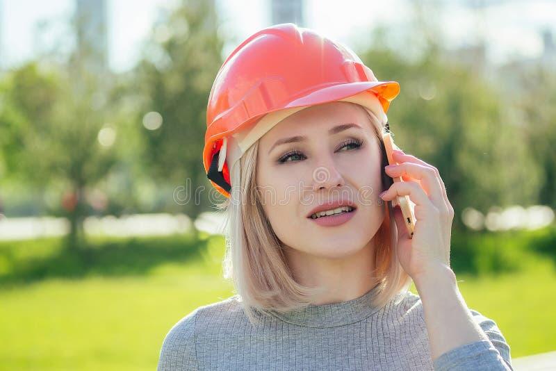 Attraktive blonde Boss Frau Builder in einem orangefarbenen Helm im Park auf einem grünen Gras stockfotos