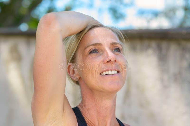 Attraktive blonde Frau mit einem durchdachten Lächeln stockfoto