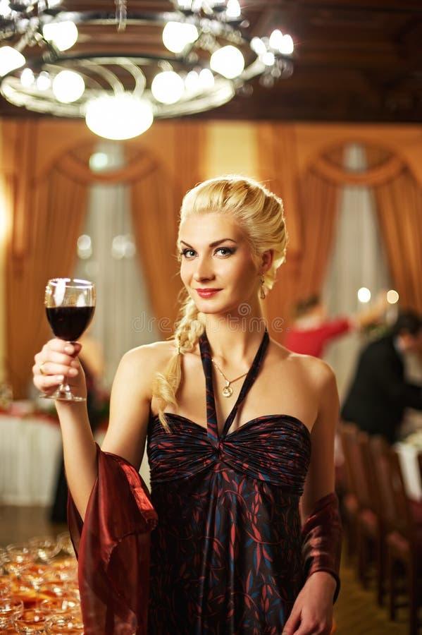 Attraktive blonde Frau mit einem Glas   stockfotografie